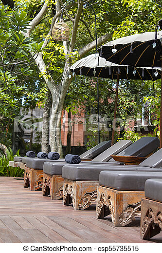 Deck chairs and umbrellas in tropical garden near swimming pool on the  beach in Bali, Indonesia