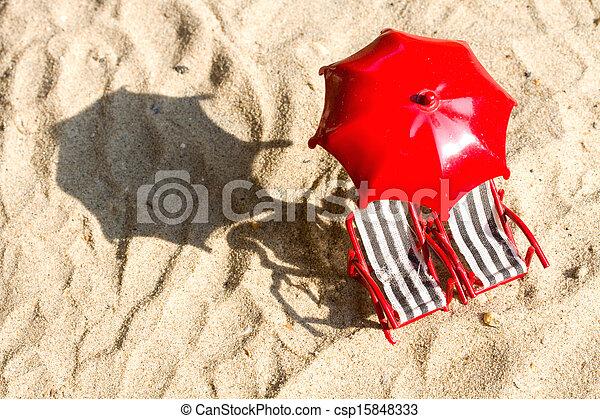 Dos sillas en miniatura en la playa con paraguas - csp15848333