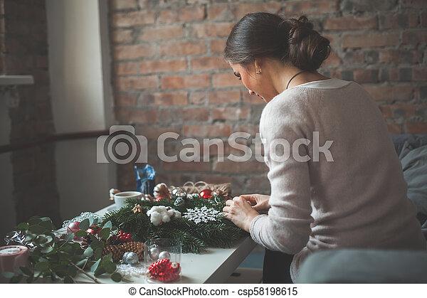 Una buena mujer haciendo decoración navideña en casa - csp58198615