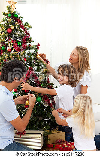 Feliz familia decorando el árbol de Navidad - csp3117230