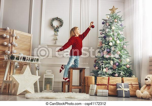 La chica está decorando el árbol de Navidad - csp41172312