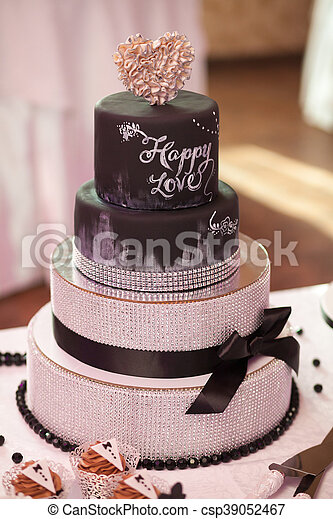 Decorated Chocolate Wedding Cake With Brown Ribbon On Table