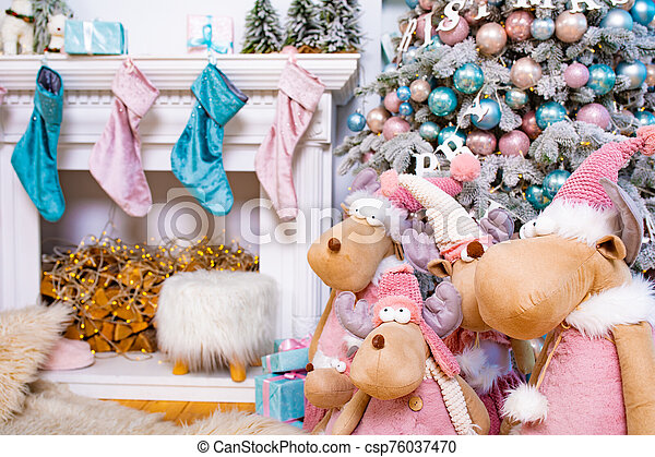 Decorated Christmas tree. Christmas mooses or deers. Many balls on the tree for the new year. Stockings on the fireplace waiting for Santa Claus. - csp76037470