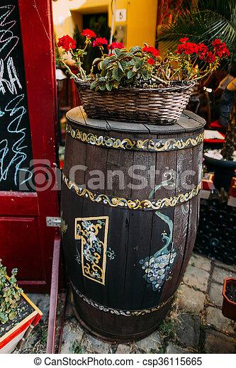 Decoration fragment of sidewalk summer restaurant in Lviv, Ukraine. Decorative wooden barrel with red flowers on it - csp36115665