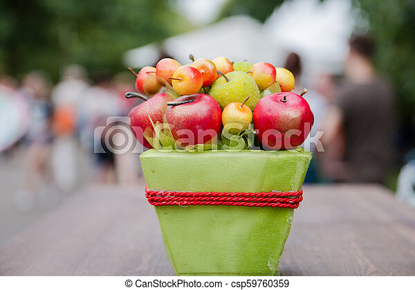 Decorative Apples In A Pot On The Background Of A Blurred Crowd Of