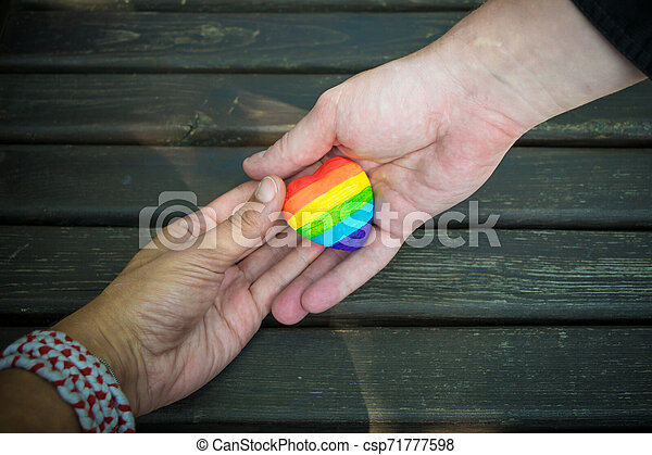 Decorative Heart with rainbow stripes in male hands. LGBT pride flag, symbol of lesbian, gay, bisexual, transgender for social movements. Homosexual love, Human rights concept. Copy space. - csp71777598
