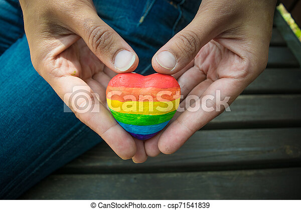 Decorative Heart with rainbow stripes in female hands. LGBT pride flag, symbol of lesbian, gay, bisexual, transgender for social movements. Homosexual love, Human rights concept. Copy space. - csp71541839