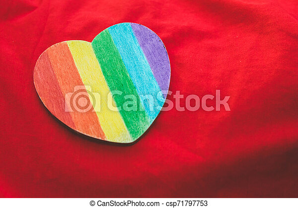 Decorative Heart with rainbow stripes on red background. LGBT pride flag, symbol of lesbian, gay, bisexual, transgender. Homosexual love, Human rights concept. Copy space. - csp71797753