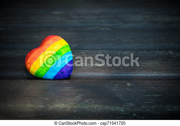 Decorative Heart with rainbow stripes on dark wooden background. LGBT pride flag, symbol of lesbian, gay, bisexual, transgender for social movements. Homosexual love, Human rights concept. Copy space. - csp71541720