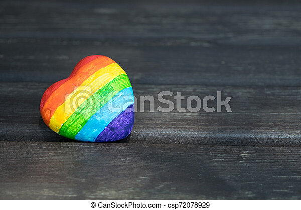 Decorative Heart with rainbow stripes on dark wooden background. LGBT pride flag, symbol of lesbian, gay, bisexual, transgender for social movements. Homosexual love, Human rights concept. Copy space. - csp72078929