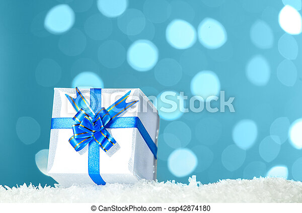 Decorative white gift box with blue bow standing in snow against - background bokeh of twinkling party lights