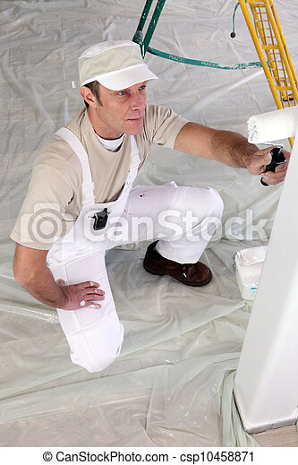 Decorator painting a room white - csp10458871