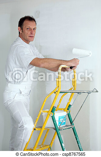 Decorator painting a room white - csp8767565