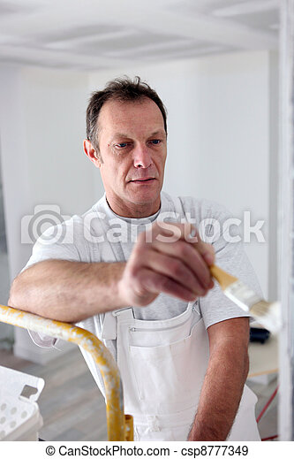 Decorator painting a room white - csp8777349