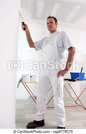 Decorator painting a room white - csp8778379