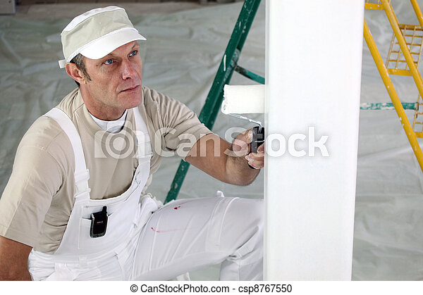 Decorator painting a room white - csp8767550