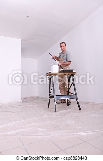 Decorator painting a room white - csp8828443