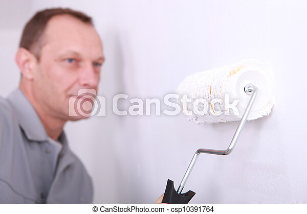 Decorator painting a room white with the roller in the foreground - csp10391764