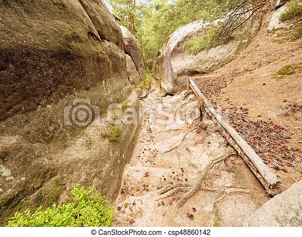 Deep entrance path in sandstone block. Historical path through forest - csp48860142
