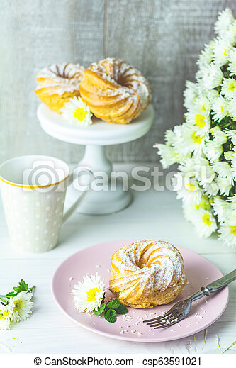 Delicious cake with coconut chips on pink plate on white table, autumn white chrysanthemum and cup of coffee - csp63591021