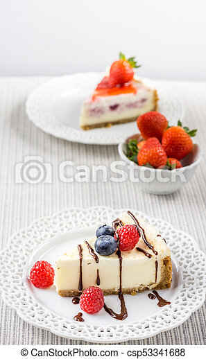 Delicious cheesecake with strawberry on a table against white wall. - csp53341688