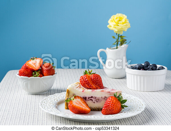 Delicious cheesecake with strawberry on a table against blue wall. - csp53341324