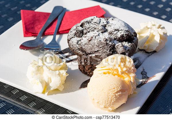 Delicious chocolate muffin served with vanilla ice cream. - csp77513470
