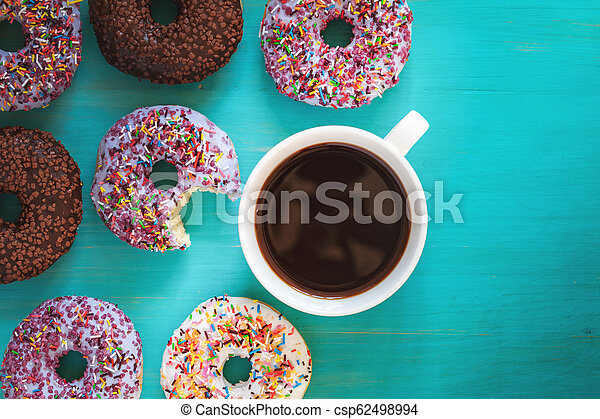 Delicious glazed donuts and cup of coffee on turquoise blue surface - csp62498994