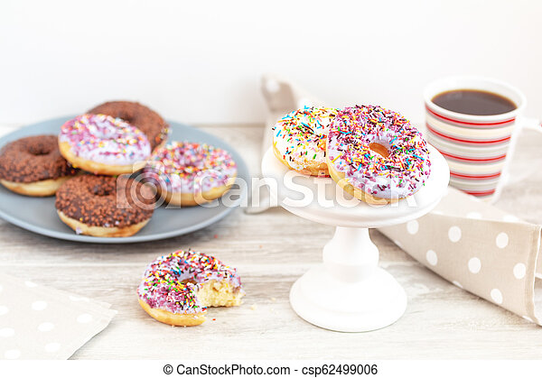 Delicious glazed donuts and cup of coffee on light wooden background - csp62499006
