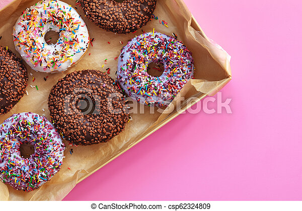 Delicious glazed donuts in box on pink surface - csp62324809