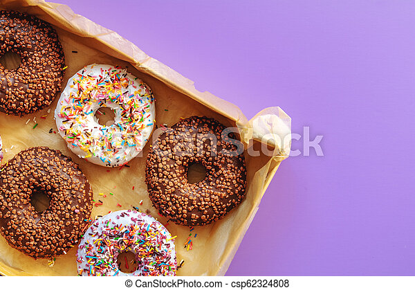 Delicious glazed donuts in box on violet surface - csp62324808