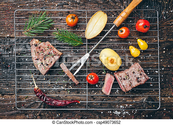 Delicious grilled steak with seasoning on wooden background - csp49073652