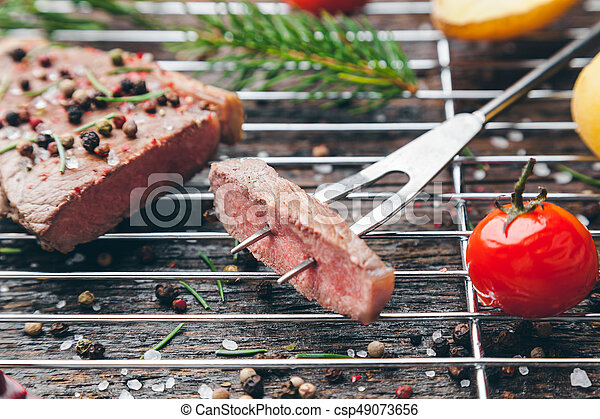 Delicious grilled steak with seasoning on wooden background - csp49073656