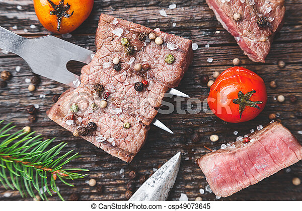 Delicious grilled steak with seasoning on wooden background - csp49073645