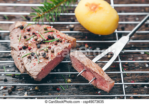 Delicious grilled steak with seasoning on wooden background - csp49073635
