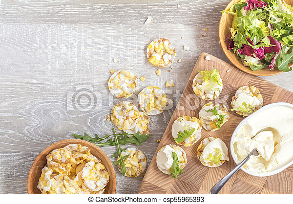Delicious nutritious cereal breads with cream cheese on kitchen table - csp55965393