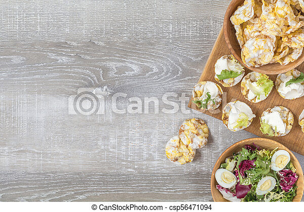 Delicious, nutritious cereal breads with cream cheese on kitchen table among some kitchen items. - csp56471094