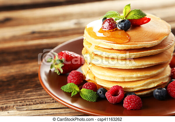 Delicious pancakes with berries on brown wooden background - csp41163262