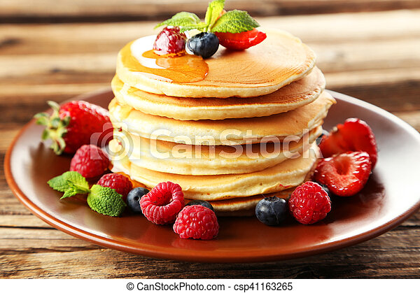 Delicious pancakes with berries on brown wooden background - csp41163265