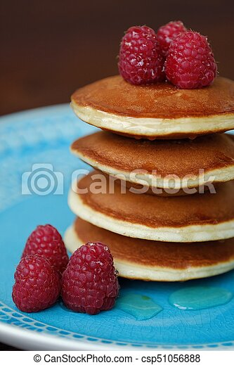 Delicious pancakes with raspberries and honey in a bowl - csp51056888