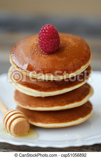 Delicious pancakes with raspberries and honey in a bowl - csp51056892