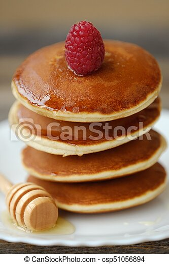Delicious pancakes with raspberries and honey in a bowl - csp51056894