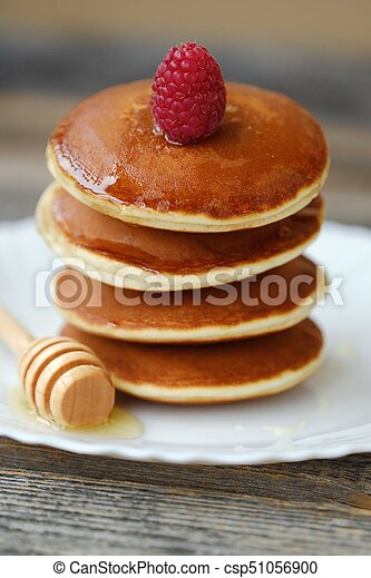 Delicious pancakes with raspberries and honey in a bowl - csp51056900