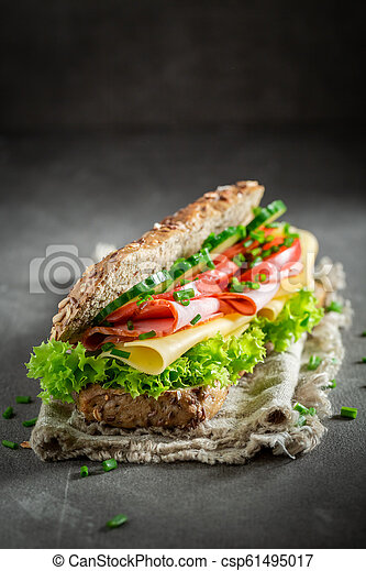 Delicious sandwich with cheese, ham and cucumber for breakfast - csp61495017