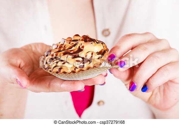 Delicious sweet cupcake in human hands. Gluttony - csp37279168