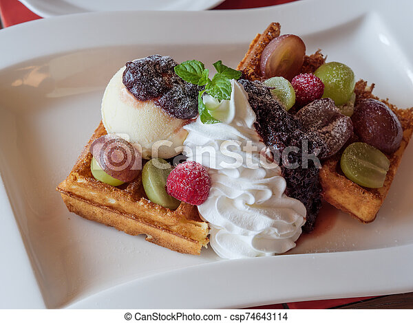 Delicious waffles with fresh fruits, ice cream and whipped cream - csp74643114