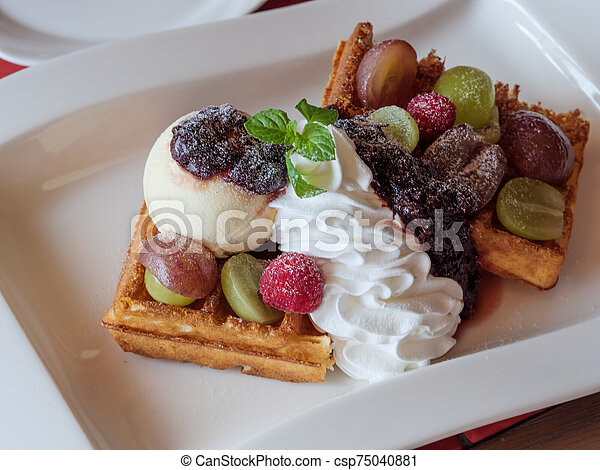 Delicious waffles with fresh fruits, ice cream and whipped cream - csp75040881