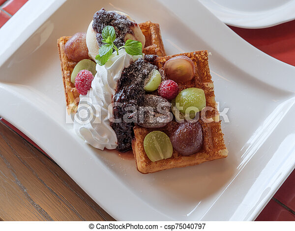 Delicious waffles with fresh fruits, ice cream and whipped cream - csp75040797