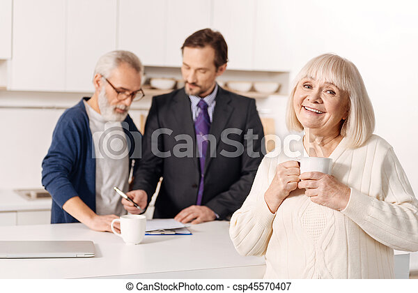 Delighted elderly woman relaxing while her husband getting the insurance - csp45570407
