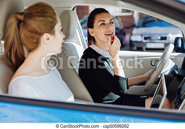 Decorative cosmetics. Delighted nice attractive businesswoman sitting in the car and holding a lipstick while painting her lips